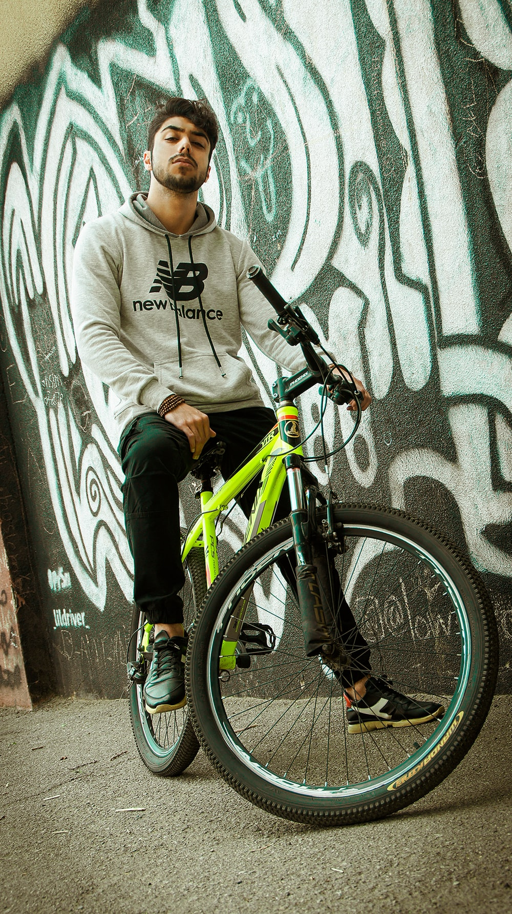 boy in gray hoodie and black pants riding on black and green mountain bike