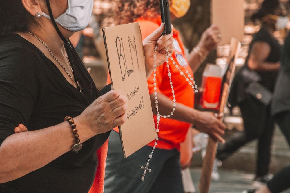 woman in black shirt holding white printer paper