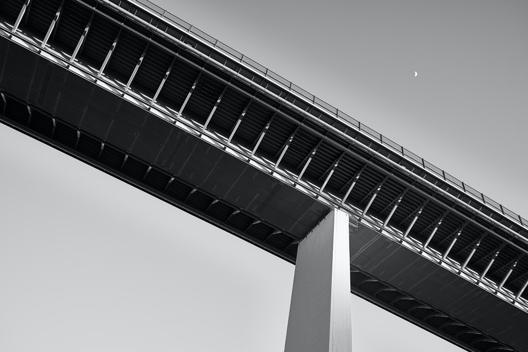Bridge photographed from below with the moon in the right corner of the picture.