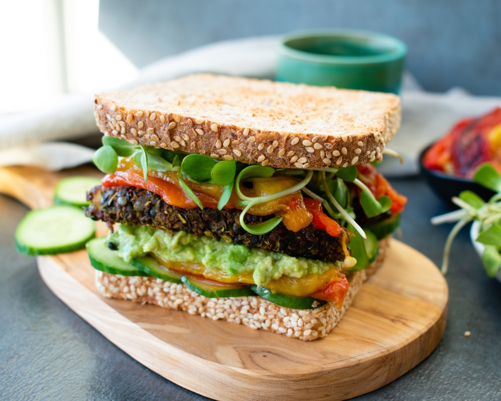 burger with lettuce and tomato on brown wooden chopping board