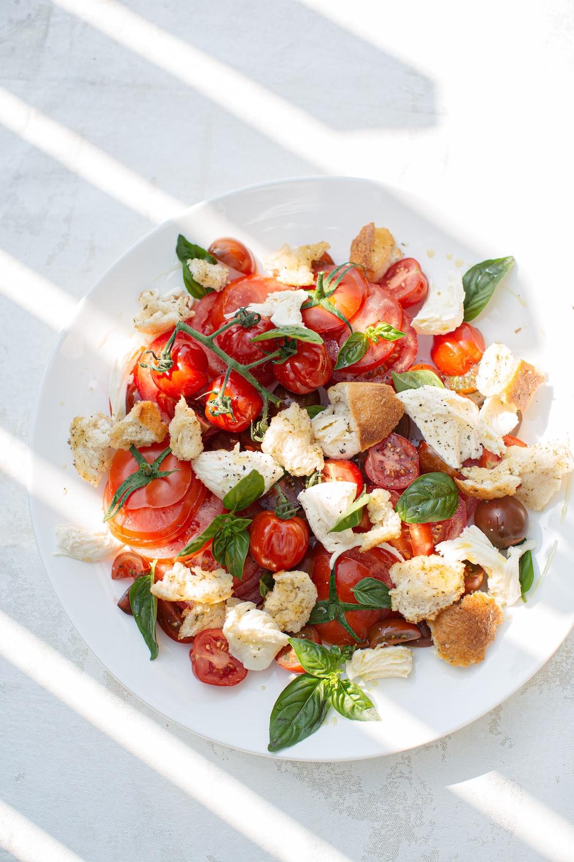 sliced tomato and green leaf vegetable on white ceramic plate