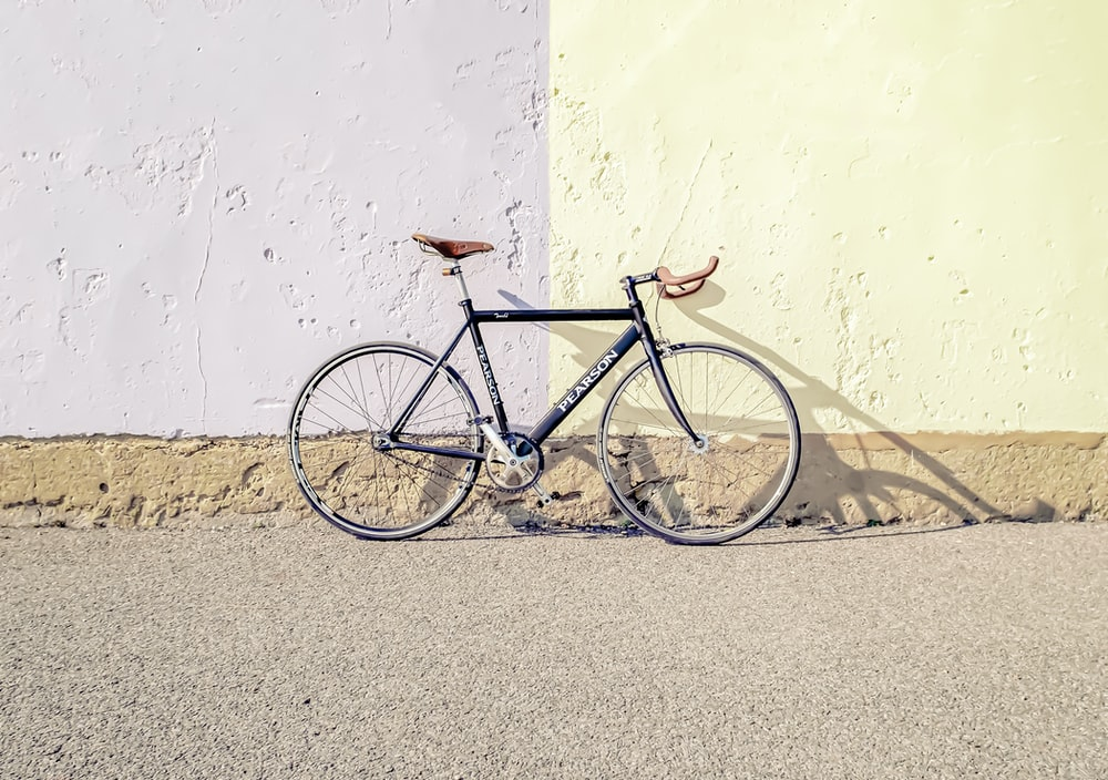 black and gray city bike leaning on white wall