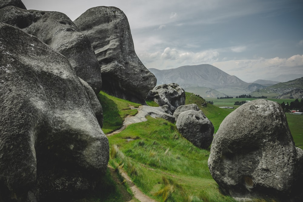 gray rock formation on green grass field during daytime