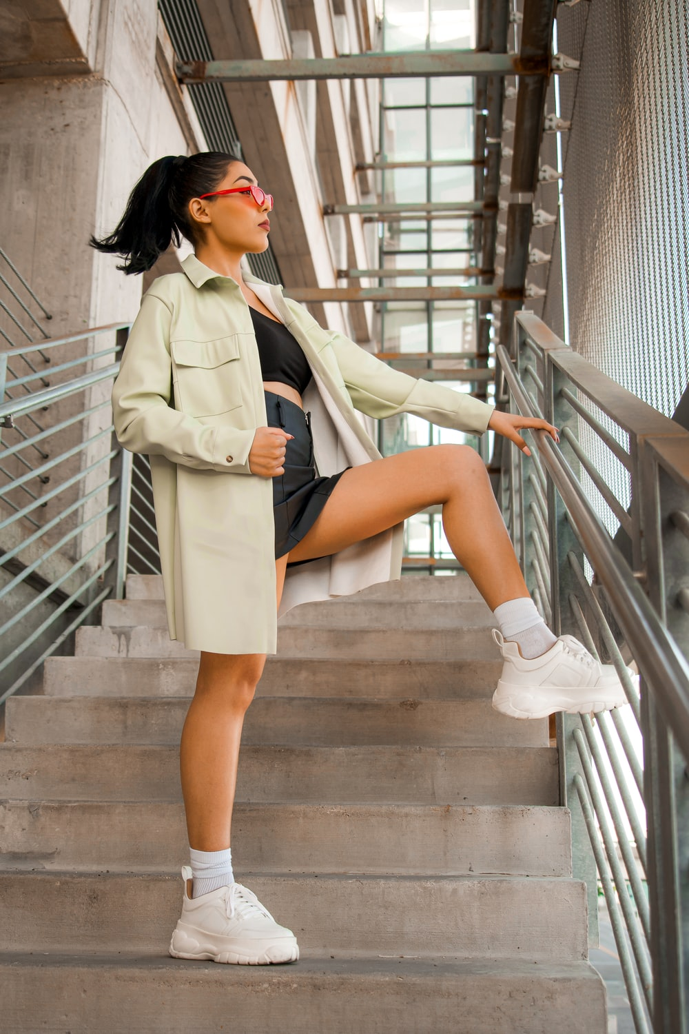 woman in white coat and black skirt sitting on brown wooden staircase