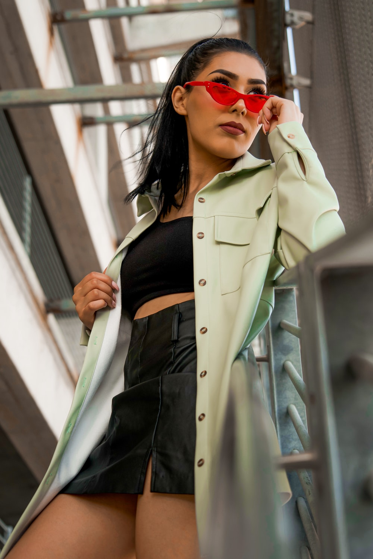 woman in beige coat and black skirt wearing sunglasses