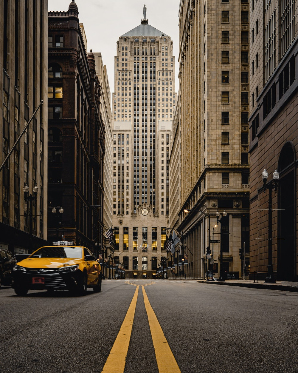 yellow car on road in between high rise buildings during daytime