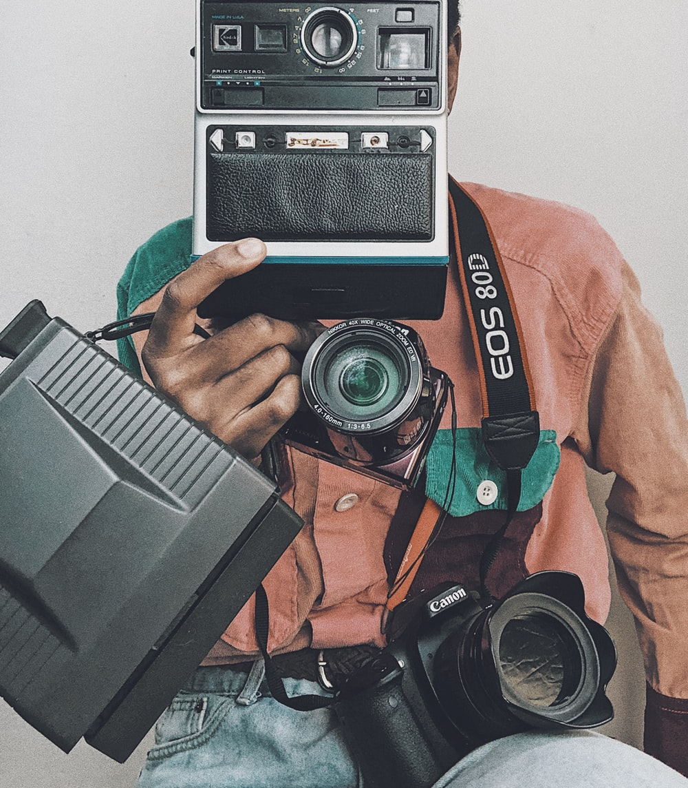 person in orange jacket holding black and gray camera