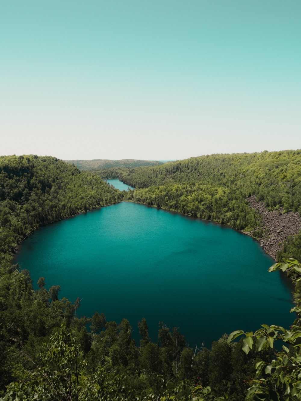 green lake surrounded by green trees during daytime