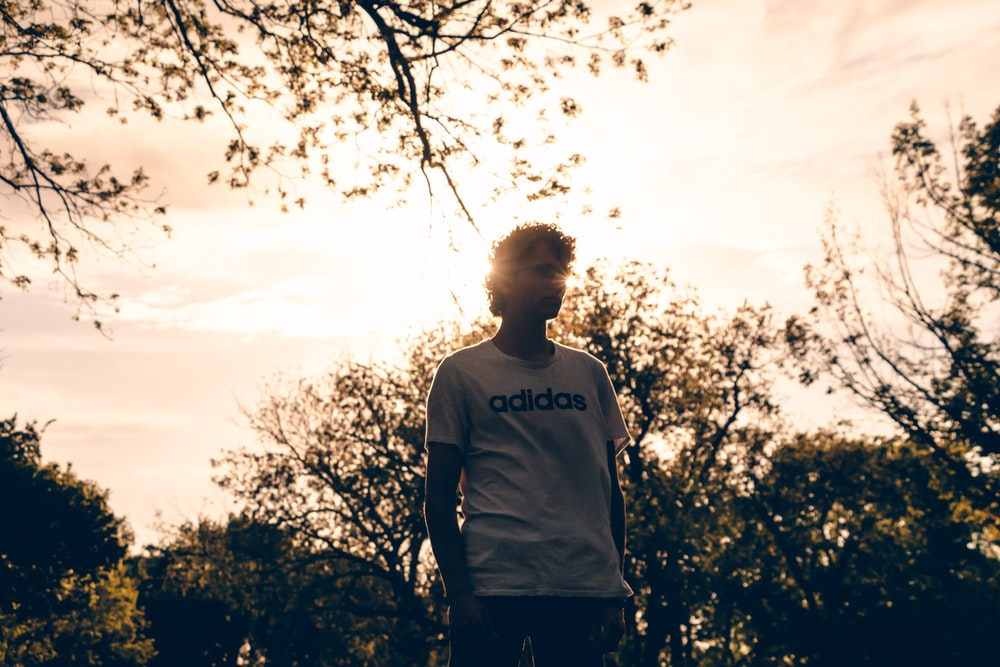 man in white and black crew neck t-shirt standing near trees during daytime