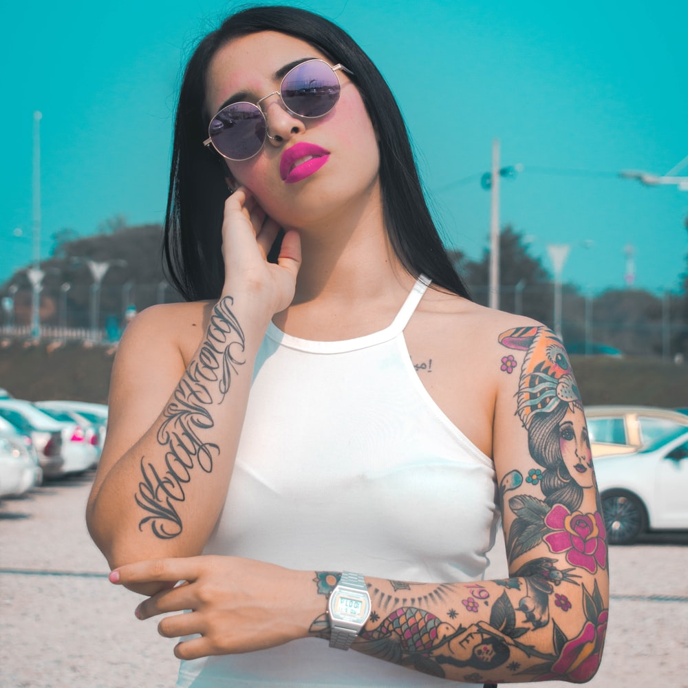 woman in white tank top with black floral tattoo on left arm