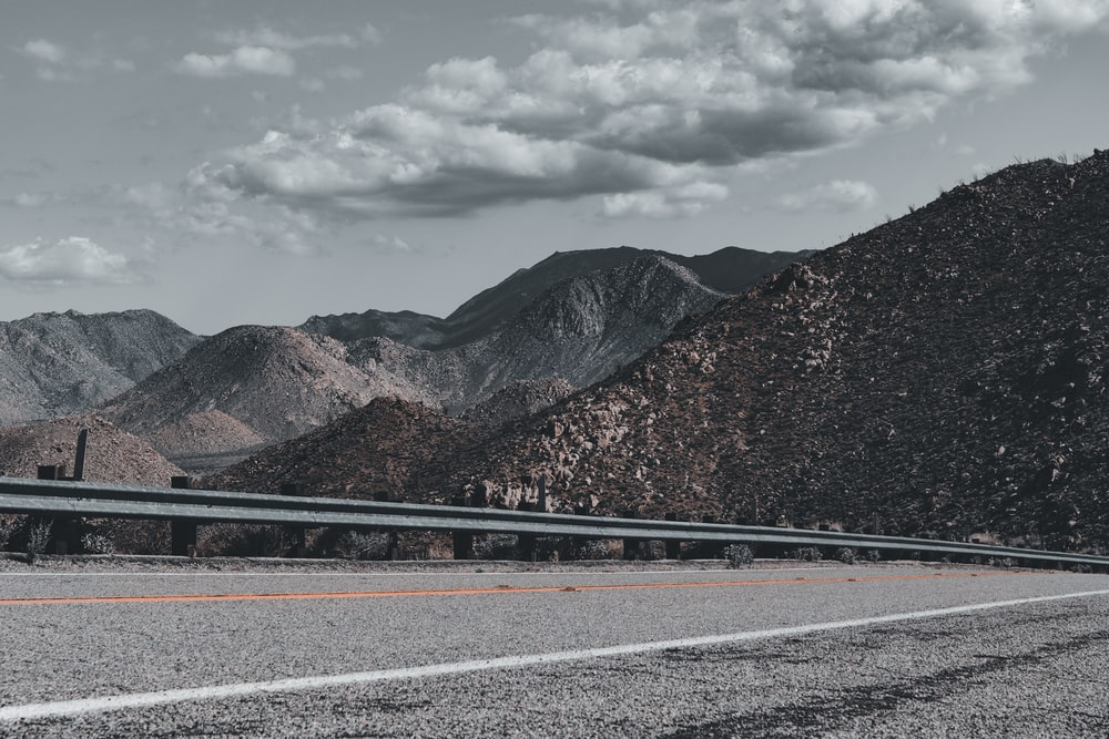 gray concrete road near brown mountain under white clouds during daytime