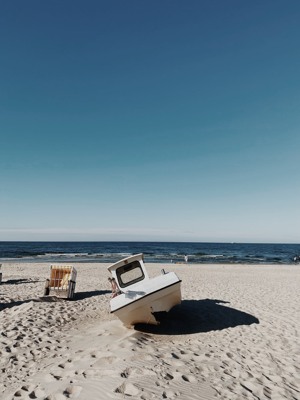 white and brown boat on beach during daytime
