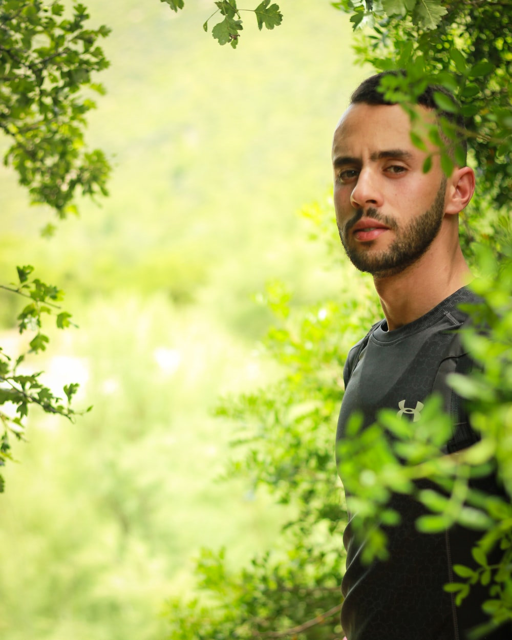 man in black and green polo shirt standing near green tree during daytime