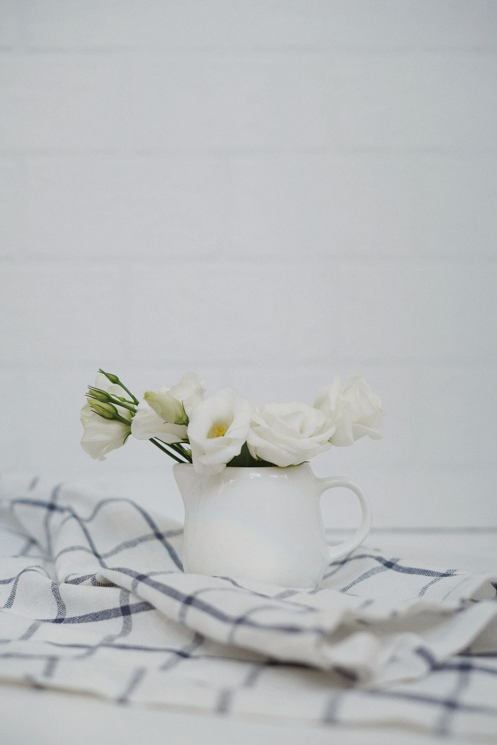 white flowers in white ceramic vase