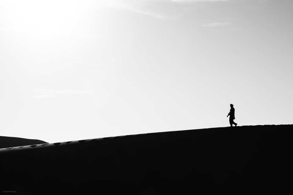 silhouette of person walking on top of the hill