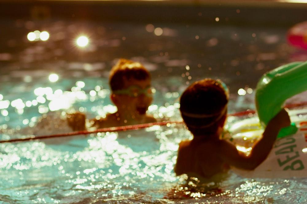 2 boys in swimming pool during daytime