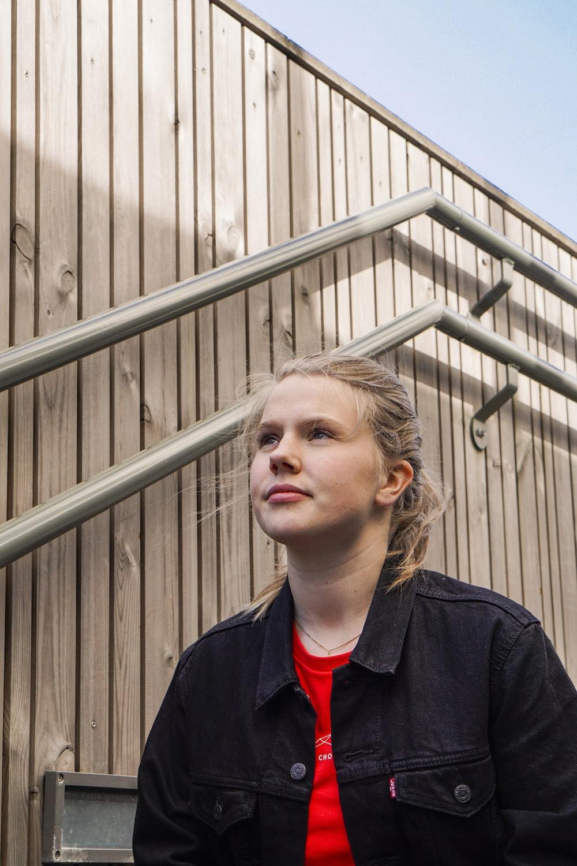 woman in black jacket standing near gray metal fence