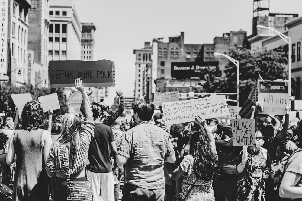 grayscale photo of people holding a banner