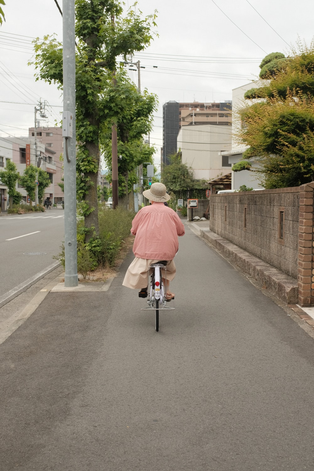 man in red dress shirt riding bicycle on road during daytime