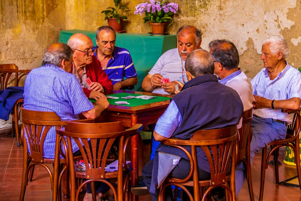 group of men sitting on chair in front of table