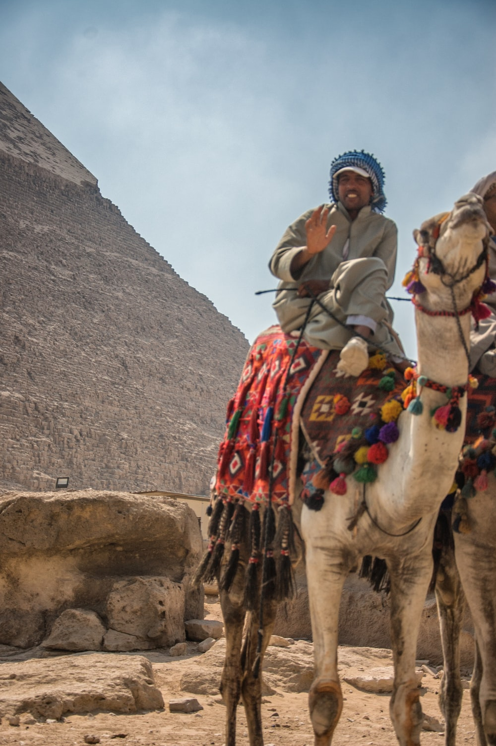 man riding camel on mountain during daytime