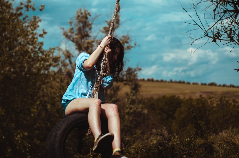woman in blue and white plaid shirt sitting on tire swing during daytime