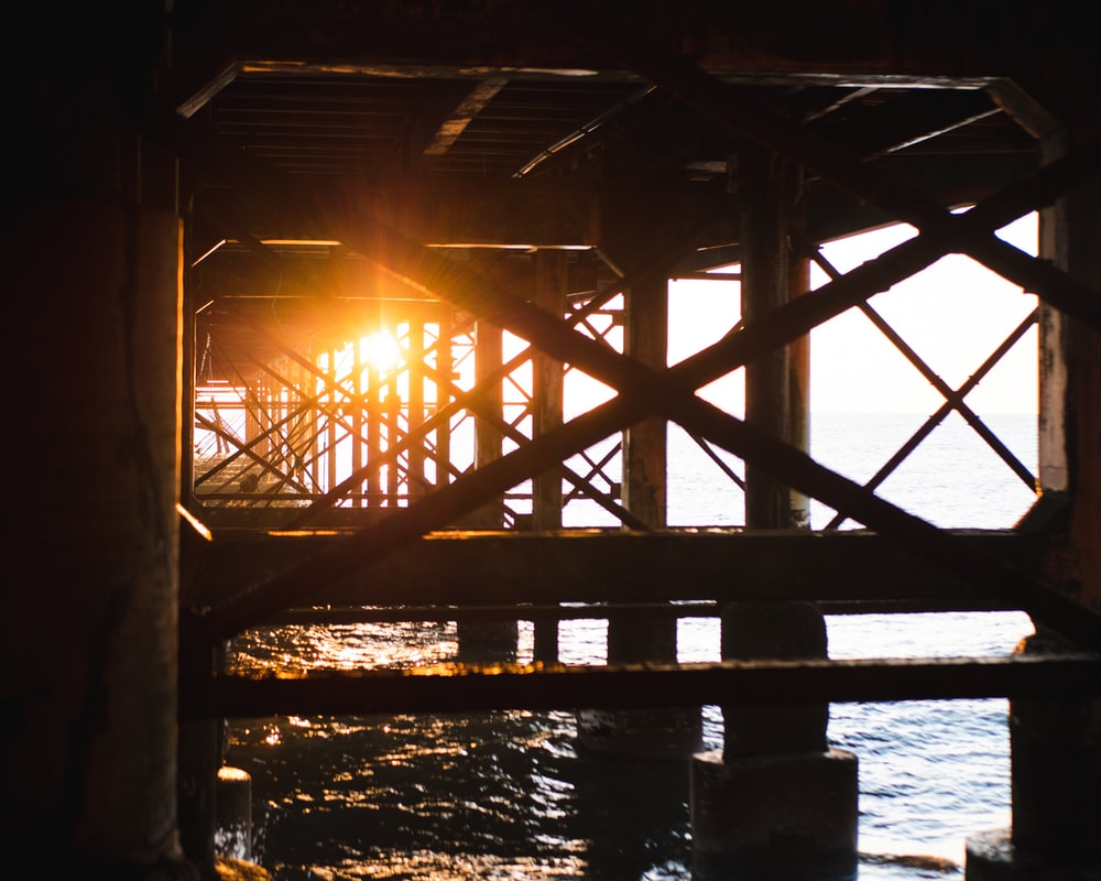 brown wooden dock over body of water during sunset