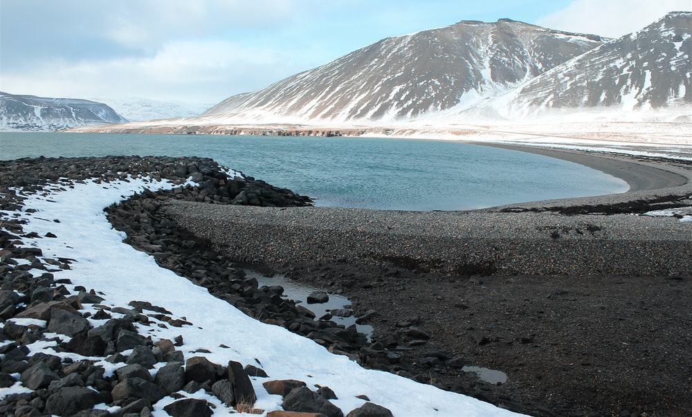 rocky shore near snow covered mountain during daytime