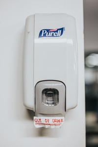 "Purell hand wash dispenser with ""out of order"" sign"