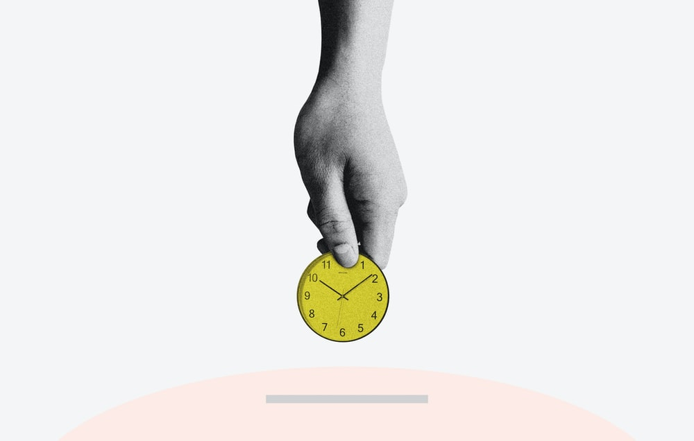 person holding yellow round analog clock