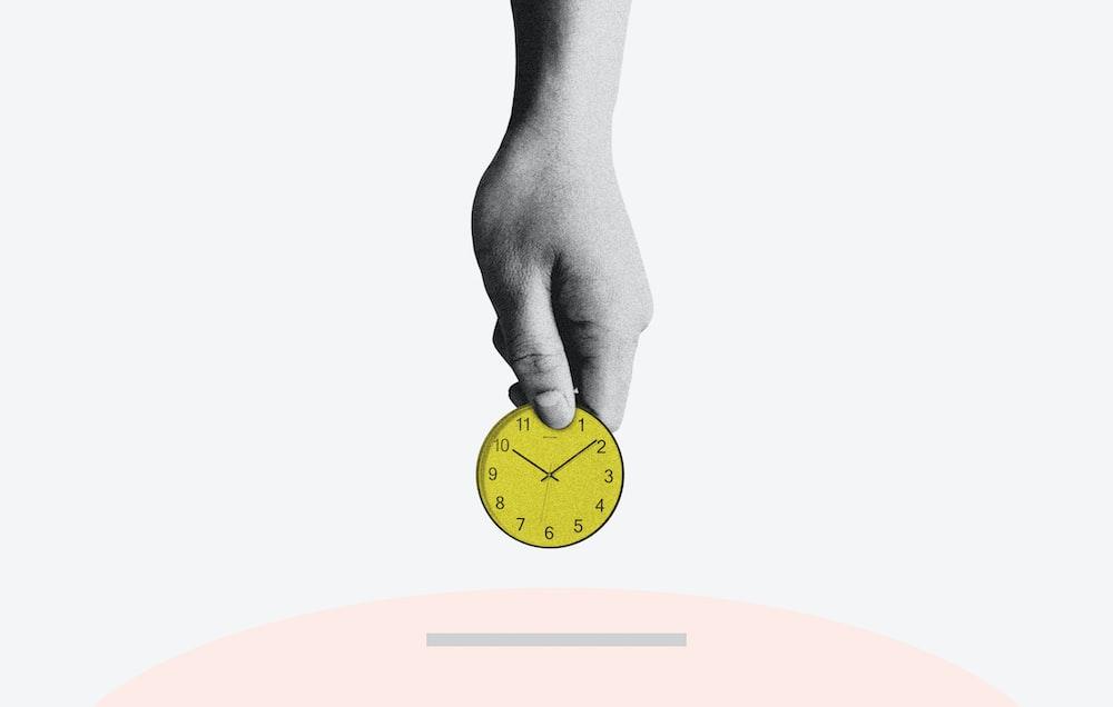 person holding yellow round analog clock
