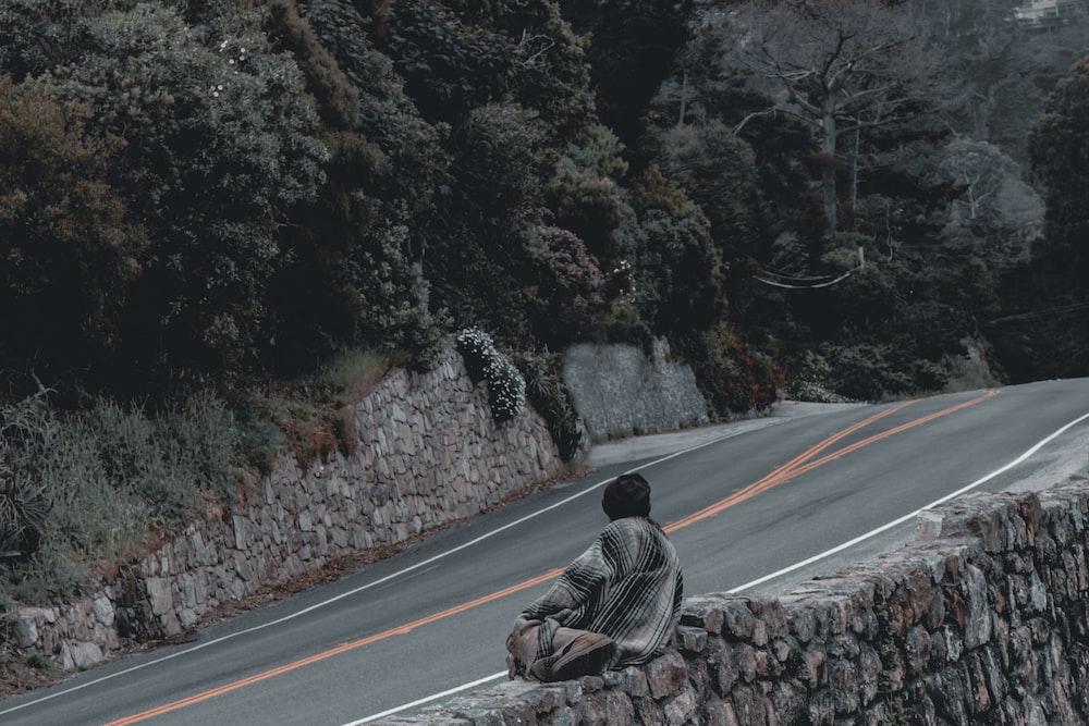 man in gray jacket sitting on gray asphalt road during daytime