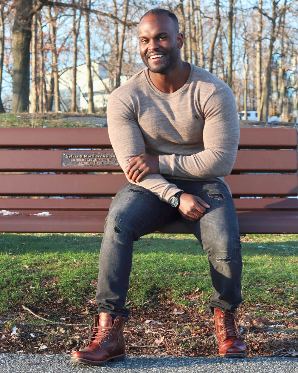 man in gray sweater and blue denim jeans sitting on brown wooden bench