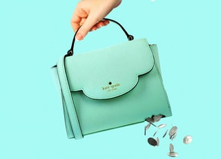 teal leather sling bag on white table