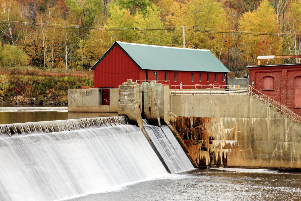 water dam near red and white house