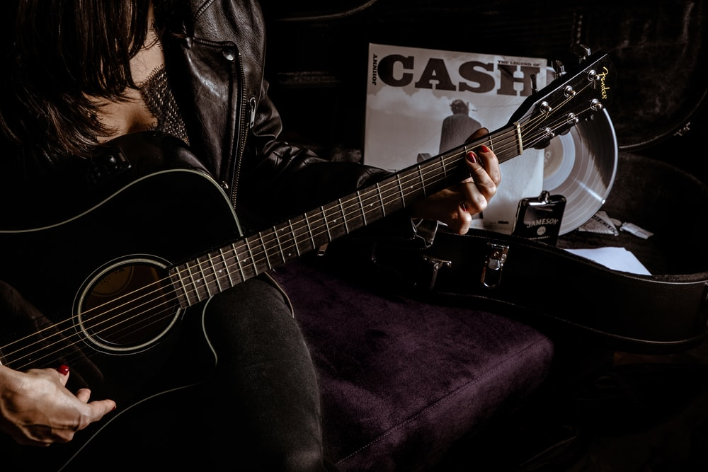 man in black leather jacket playing acoustic guitar