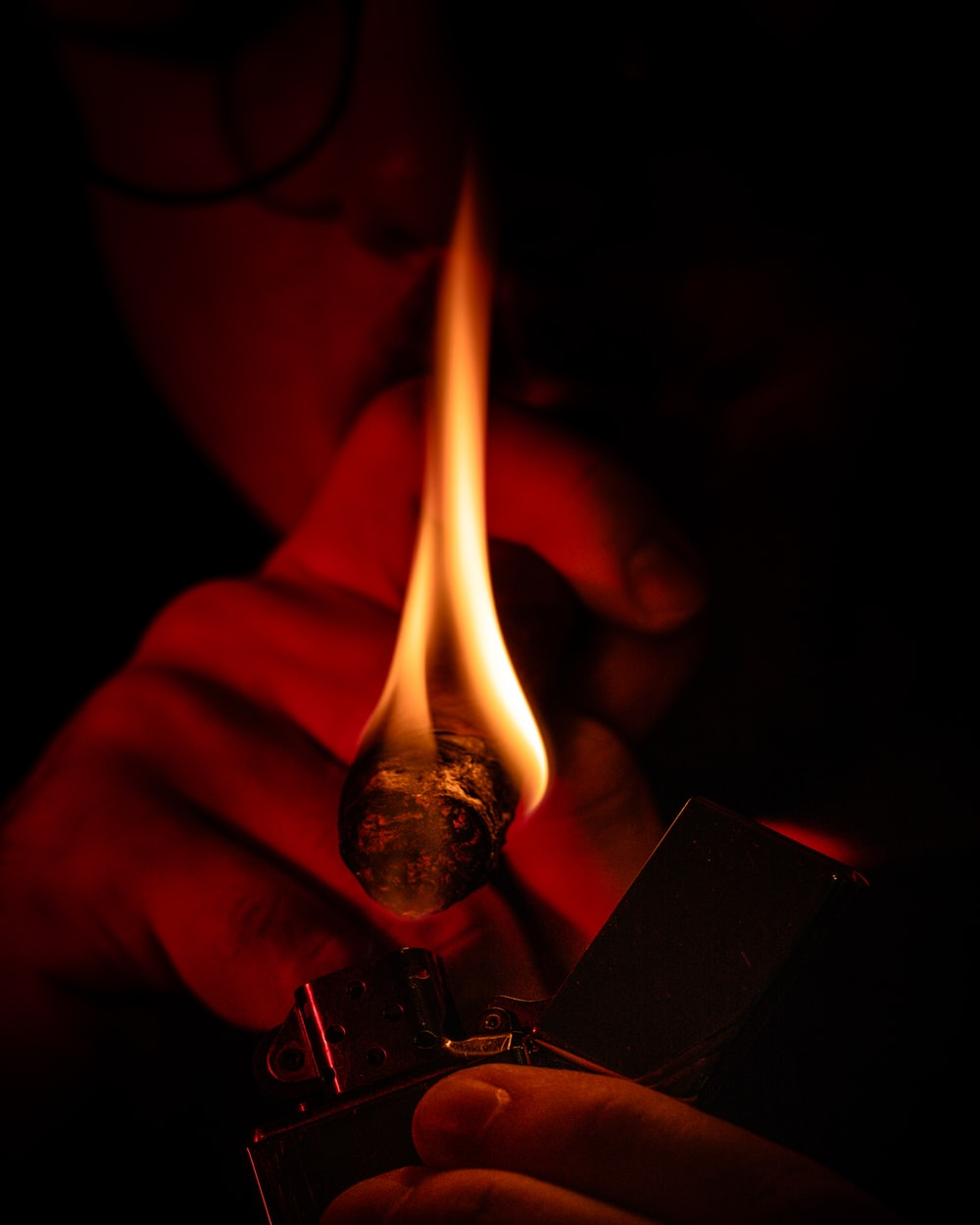 person holding lighter with fire