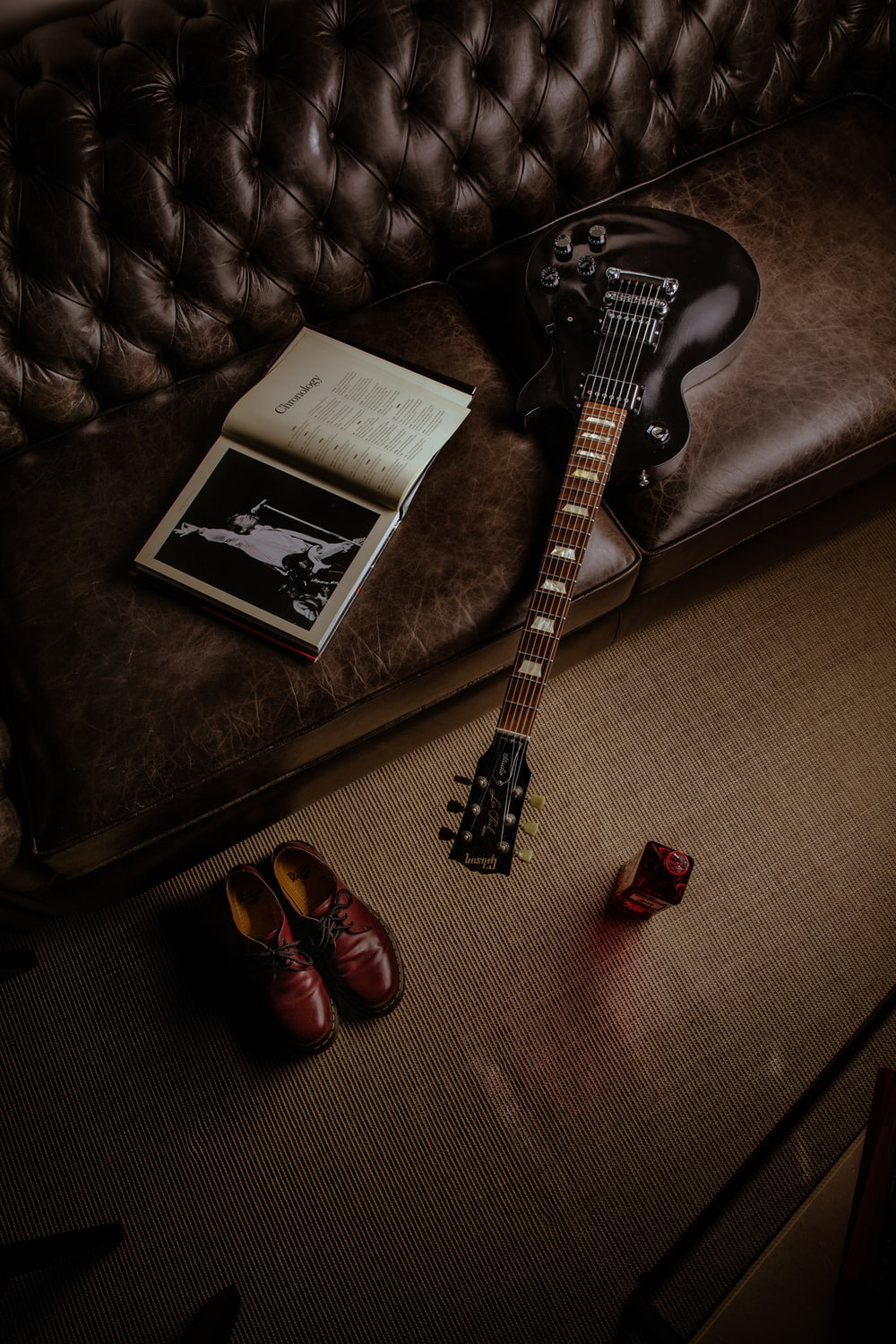 black and white stratocaster electric guitar beside black and white book