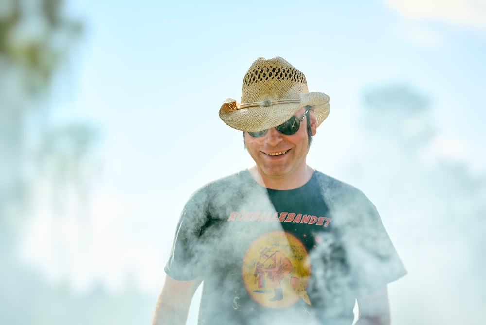 man in grey crew neck t-shirt wearing brown straw hat