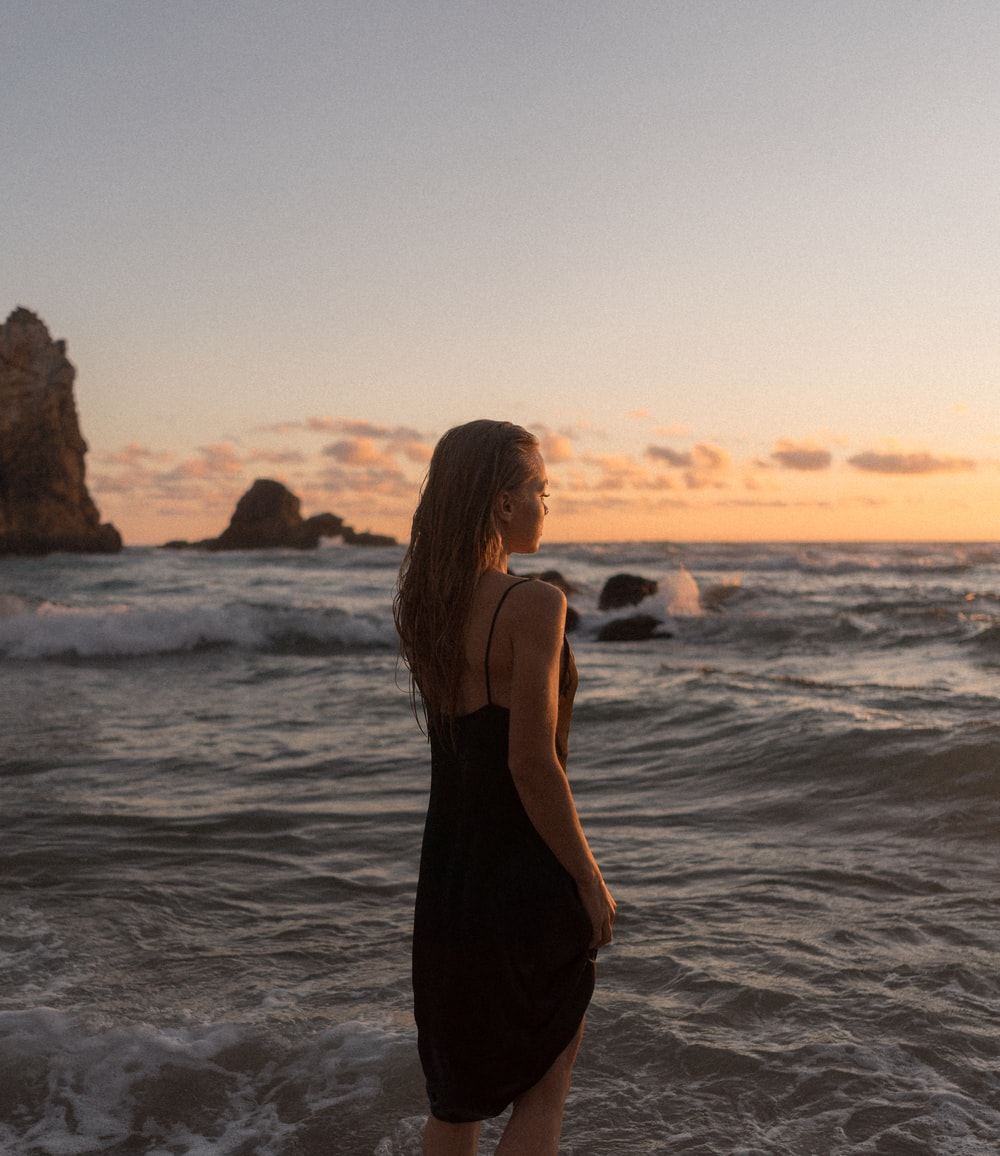 woman in black dress standing on seashore during daytime