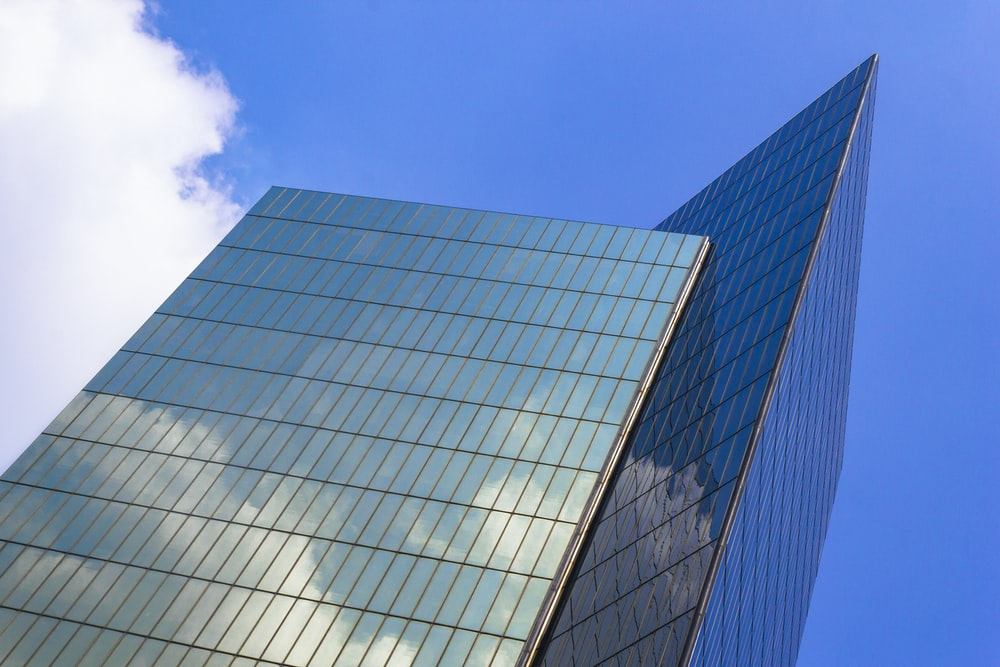 blue and white glass walled building under blue sky during daytime