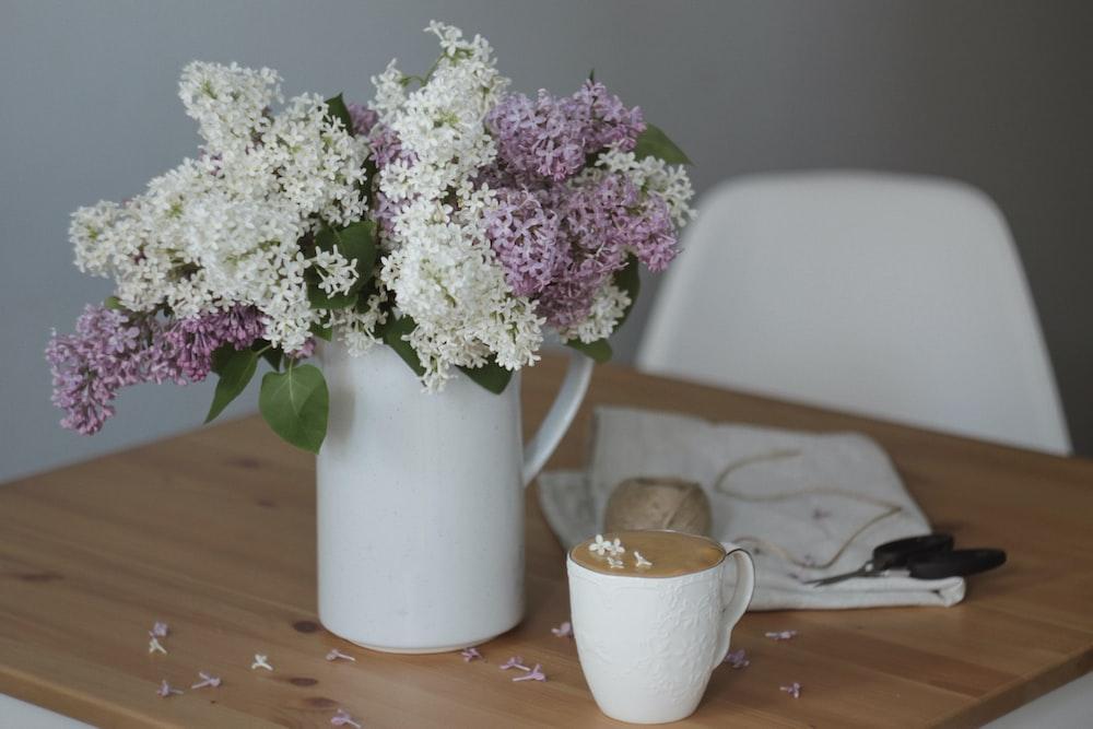 white and purple flowers in white ceramic vase