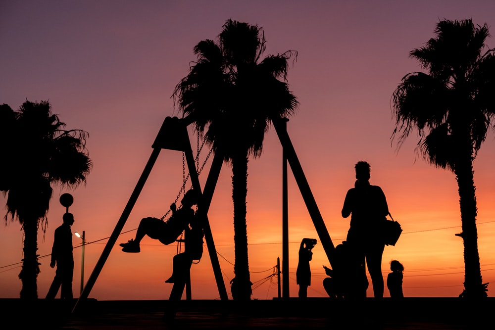 silhouette of people on swing during sunset