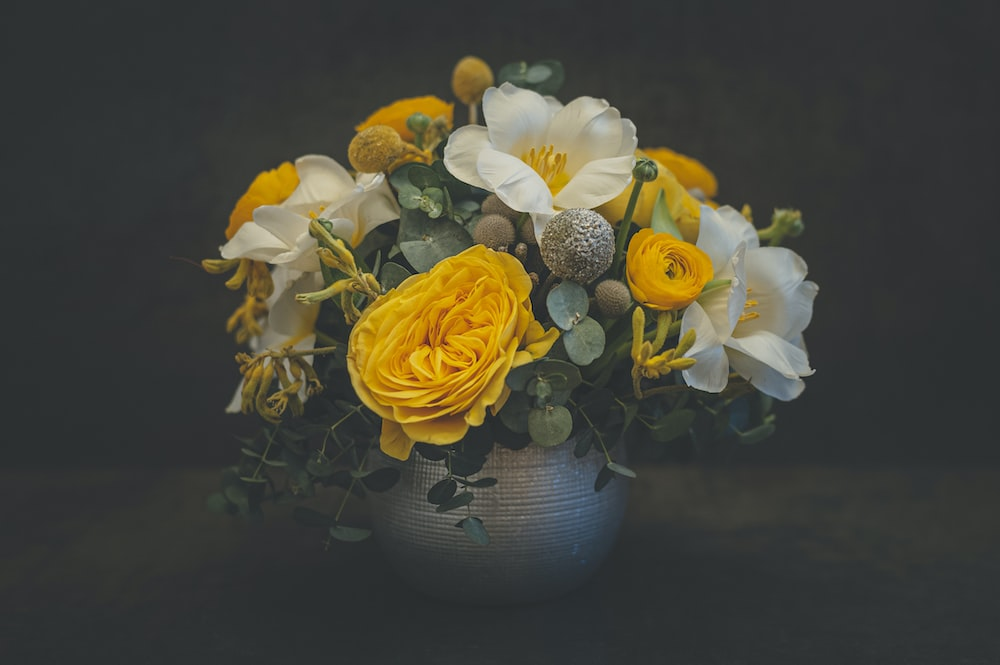 yellow and white flowers in blue ceramic vase