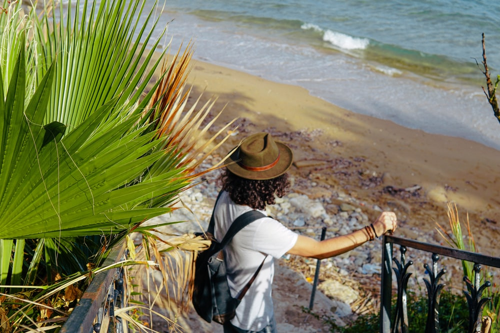 woman in white shirt and brown hat standing on beach during daytime
