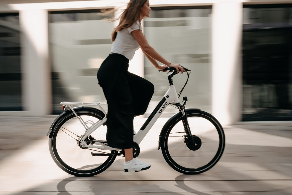 woman in white t-shirt and black pants riding on black bicycle