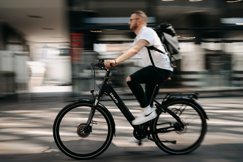 man in white dress shirt and black pants riding on bicycle
