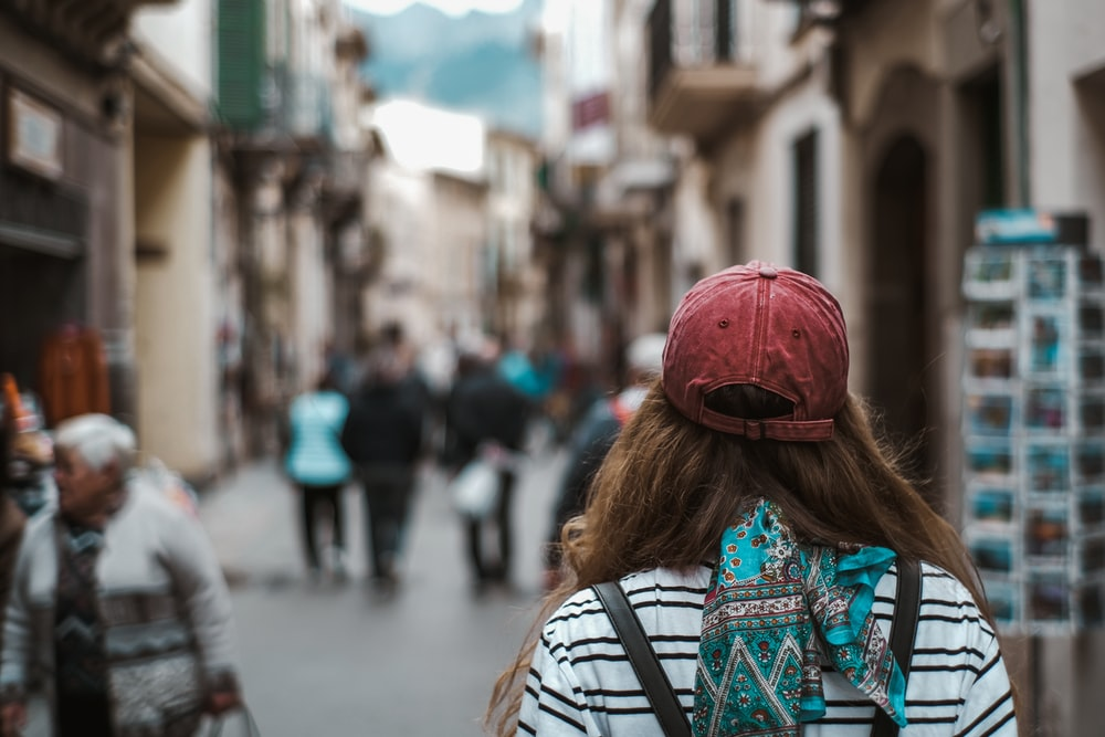 woman in red knit cap and blue and white tribal print shirt walking on street during