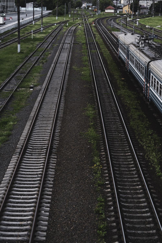 green train on rail tracks during daytime
