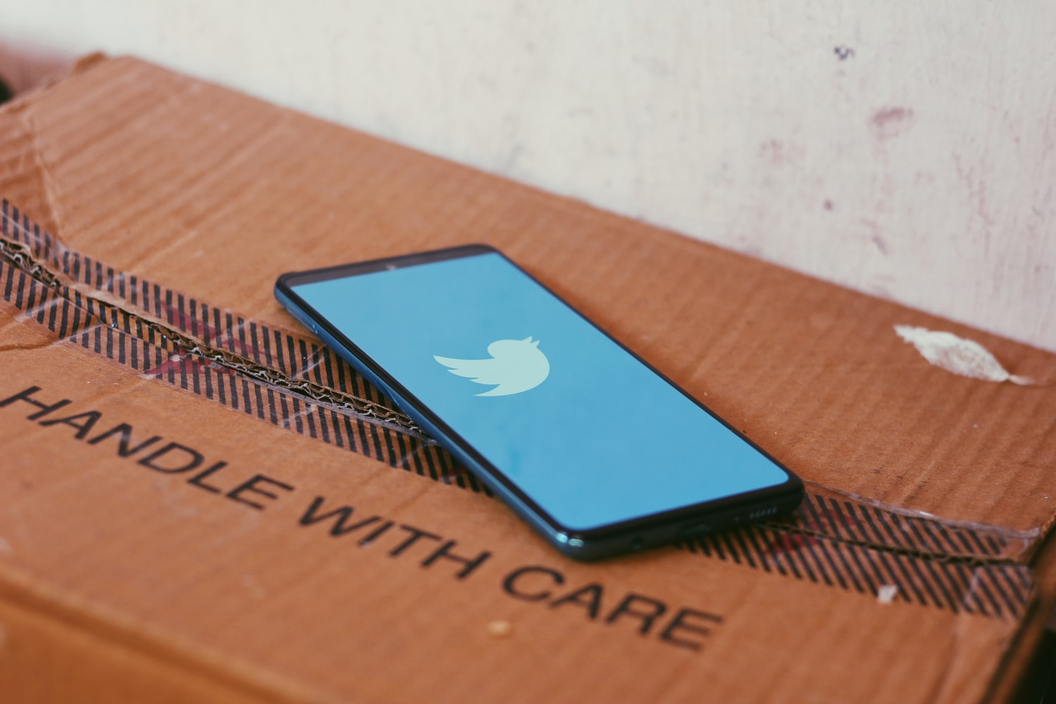 Phone showing Twitter label on a box saying 'Handle with Care'